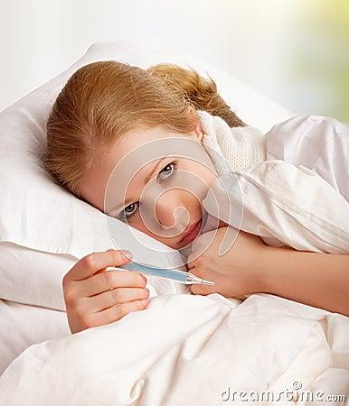 Mulher com frios doentes do termômetro, gripe, febre na cama