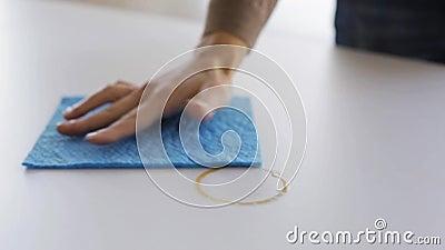Mulher com mancha do café da limpeza de pano na tabela filme