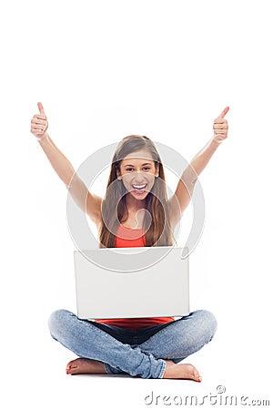 Mulher com o portátil que mostra os polegares acima