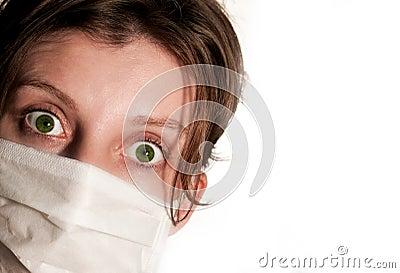 Mulher com os olhos verdes grandes que vestem a máscara médica