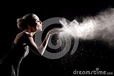 A mulher com para o movimento do pó explosivo capturado pelo flash