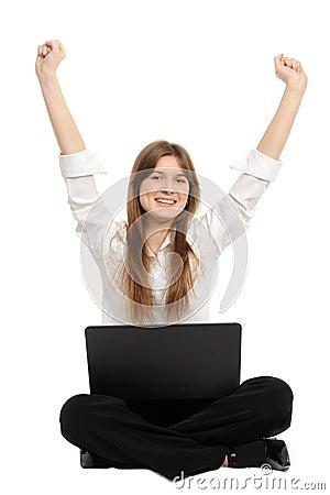 Mulher com um portátil que aprecia seu sucesso em linha