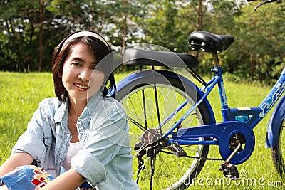 Mulher com uma bicicleta que sorri ao ar livre
