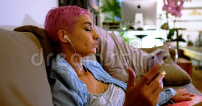 Mulher cor-de-rosa do cabelo que usa o telefone celular no sofá 4k filme