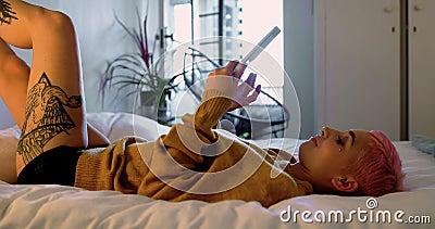 Mulher cor-de-rosa do cabelo que usa a tabuleta digital na cama no quarto 4k vídeos de arquivo