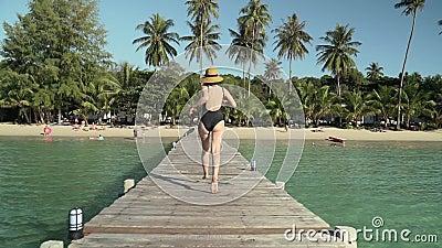 Mulher corre em um cais de madeira para praia tropical video estoque