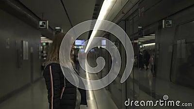 Mulher da cidade no trem de espera da estação de metro na plataforma Jovem mulher do viajante no subterrâneo Menina no modernmetr filme