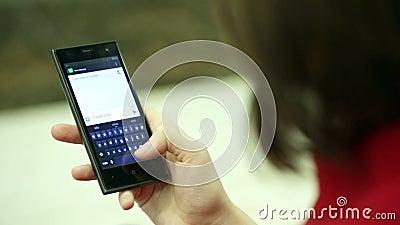 Mulher de datilografia em um close-up do dispositivo do smartphone vídeos de arquivo