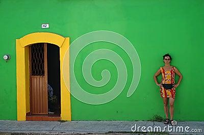 Mulher de encontro à parede verde
