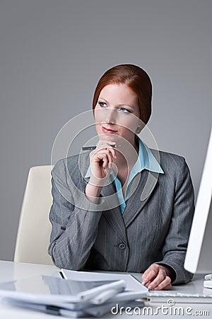Mulher de negócio bem sucedida no pensamento do escritório