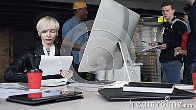 Mulher de negócio nova bem sucedida que trabalha no escritório moderno usando o tela táctil do computador, olhando o monitor Equi video estoque