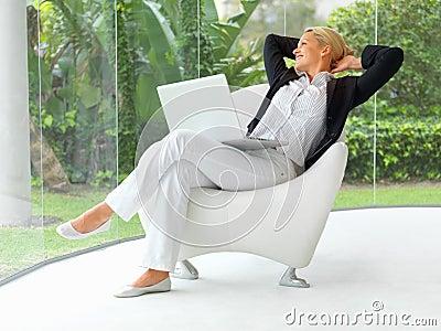 Mulher de negócio que senta-se em uma cadeira com portátil