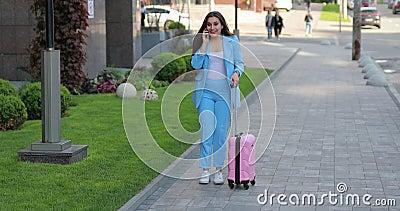 Mulher de neg?cios com mala de viagem que fala pelo telefone na cidade e para ter uma boa not?cia vídeos de arquivo