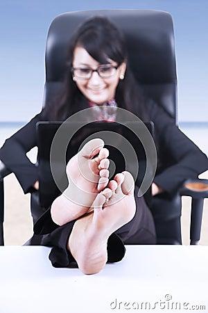 A mulher de negócios feliz relaxa na praia