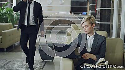 Mulher de negócios loura que senta-se na poltrona com bloco de notas e laptop quando homem de negócios com bagagem que anda compl video estoque