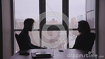 Mulher de negócios na mesa, que faz perguntas ao homem oposto Jovens empregadas entrevistam homens em um escritório filme