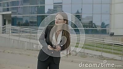 Mulher de negócios nova com o cabelo longo que veste o equipamento formal que espera o táxi do uber e que olha ao redor após um o filme