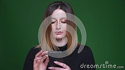 Mulher de negócios nova com os relógios do cabelo da castanha no telefone celular na perplexidade e na confusão no fundo verde video estoque