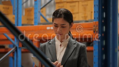 Mulher de negócios nova que usa a tabuleta digital que verifica o estoque no armazém industrial