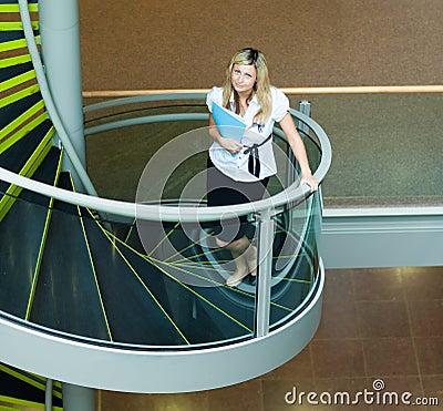 Mulher de negócios que anda acima das escadas no escritório