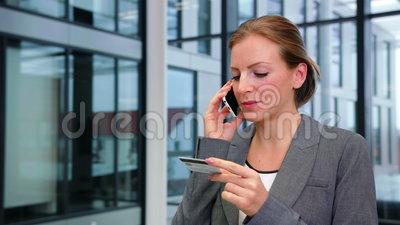 Mulher de negócios que usa o cartão de crédito ao falar no telefone celular filme