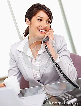 Mulher de negócio nova que tem uma conversa telefónica