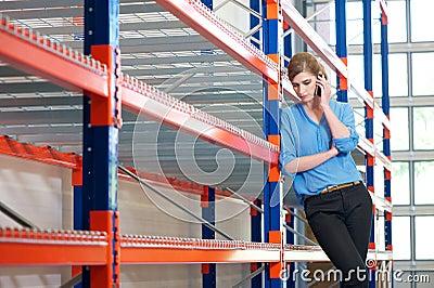 Mulher de negócio segura no telemóvel no armazém