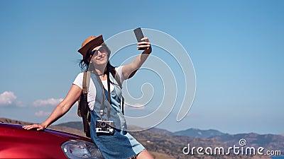 Mulher de sorriso bronzeada bonita do curso que aprecia as férias que tomam o selfie usando o smartphone tiro médio filme