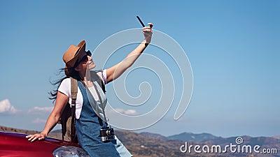 Mulher de sorriso do curso com o cabelo de ondulação que levanta na capota do carro que toma o selfie usando o smartphone filme