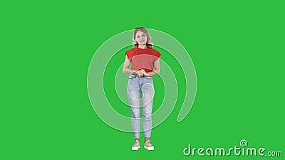Mulher de sorriso na roupa ocasional que apresenta algo, empurrando botões imaginários em uma tela verde, chave do croma video estoque