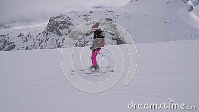 A mulher do esquiador do novato está esquiando abaixo da inclinação sob os elevadores vídeos de arquivo