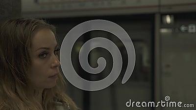 Mulher do retrato no trem de espera da estação de metro na plataforma Jovem mulher do viajante no subterrâneo Menina no moderncit vídeos de arquivo