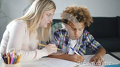 A mulher e o pequeno rapaz africano estão aprendendo um novo exercício escolar escrevendo tarefa em casa vídeos de arquivo