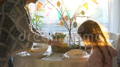 A mulher e sua filha pequena estão ajustando a tabela festiva de easter com coelho e estão eggs a decoração filme