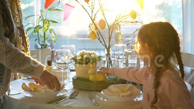 A mulher e sua filha pequena estão ajustando a tabela festiva de easter com coelho e estão eggs a decoração video estoque