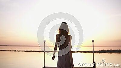 Mulher elegante, bonita com cabelo marrom no vestido de seda cinzento elegante que anda em um cais sunlight Acima do mar video estoque