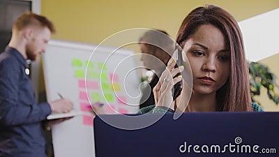 Mulher empresária usando um smartphone e um laptop em uma mesa no escritório produtivo filme
