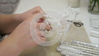 A mulher entrega a agulha que costura os grânulos brancos para o acessório do cabelo filme