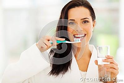 A mulher escova os dentes