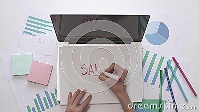 A mulher escreve o SALÁRIO em um pedaço de papel situado no portátil Vista superior filme