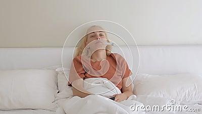 A mulher está em casa na cama, trocando os canais de TV de controle remoto e medindo sua temperatura com um aparelho eletrônico filme