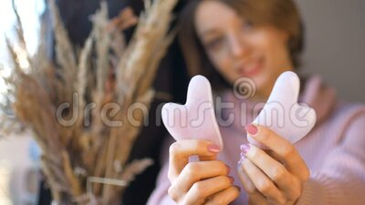 A mulher está mostrando uma massagem na água, massageada feita de quartzo de roseira natural em forma de coração, que é usada filme