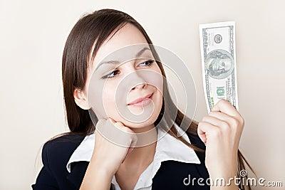 A mulher está olhando 100 dólares de nota de banco