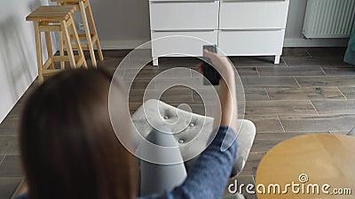 A mulher está sentada em uma cadeira, assistindo TV com tela verde, trocando canais com controle remoto Tecla croma vídeos de arquivo