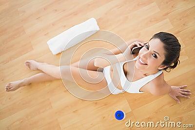 A mulher feliz apta que toma uma chamada durante seu exercício que olha veio