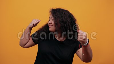 Mulher feliz com excesso de peso mantendo punhos levantados, dançando, fazendo gestos vencedores video estoque