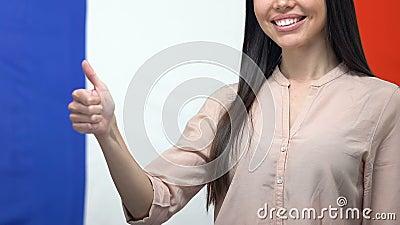 Mulher feliz mostrando polegares para cima, fundo de bandeira francesa, curso de língua estrangeira filme