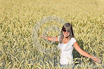 A mulher feliz no campo de milho aprecia o por do sol