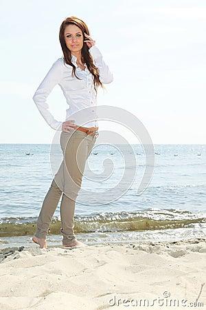 A mulher feliz nova em uma praia