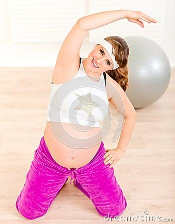 Mulher gravida de sorriso que faz exercícios da aptidão